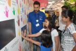 Children enjoying demo of hand print technology in Science Express Climate Action Special